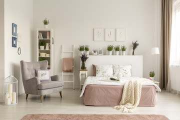 Real photo of a feminine bedroom interior with a comfy armchair, bed, plants and shelf