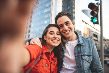 Say cheese. Waist up portrait of smiling young man and woman sightseeing with delight. They are bonding to each other and making selfie with camera