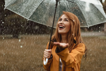 Waist up portrait of smiling pretty female enjoying rainy weather. She is standing under umbrella and stretching hand catching water drops with content Fototapete