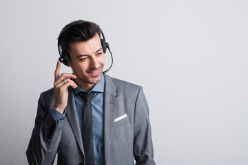 Portrait of a young man with headset in a studio. Copy space.