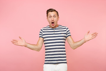 Portrait of surprised shocked man wearing striped t-shirt spreading hands gesture on copy space isolated on trending pastel pink background. People sincere emotions lifestyle concept. Advertising area