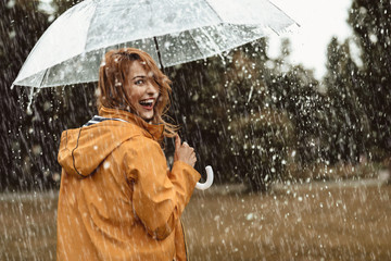 Cheerful pretty girl holding umbrella while strolling outside. She is turning back and looking at camera with true delight and sincere smile. Copy space in right side