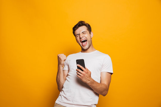 Portrait of a joyful young man holding mobile phone