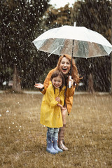 Full length of joyful child standing near mother in raincoat. Content woman is holding umbrella and stretching hand with excitement