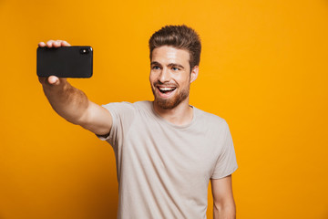 Portrait of a happy young man taking a selfie