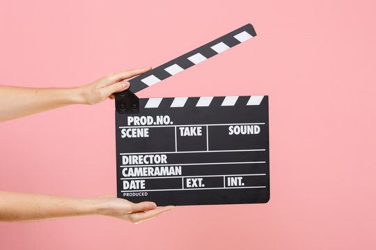 Close up female holding in hand classic director clear empty black film making clapperboard isolated on trending pastel pink background. Cinematography production concept. Copy space for advertising.