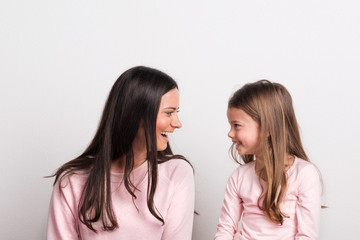 A small girl and her mother looking at each other in a studio.