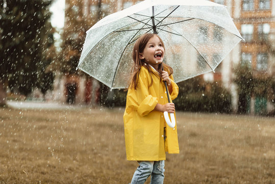 Waist up portrait of joyful kid spending time outside standing with umbrella in hands. She is looking upwards with content and sincere smile