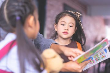 Teacher is reading story book to kindergarten students Kid