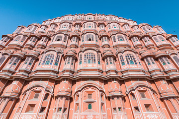 View of Hawa Mahal (Palace of Winds or Palace of the Breeze) with blue sky in background. It's constructed of red and pink sandstone, located on the edge of City Palace, Jaipur, Rajasthan, India