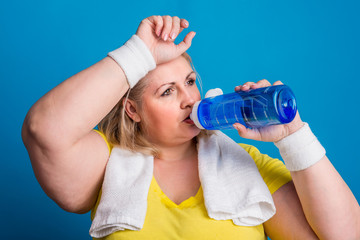 Portrait of a tired overweight woman in studio on a blue background, drinking water.