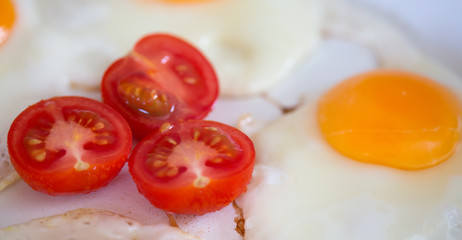 Fried eggs with cherry tomatoes .