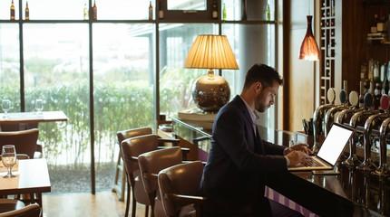Businessman using laptop at counter