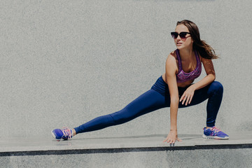 Active fit woman in sportsclothes does morning stretching, stands in pose, prepares for run, wears comfortable clothes and sportshoes, poses outdoor. People, sport, workout, lifestyle concept