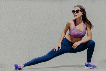 People, sport and motivation concept. Full length shot of athletic sporty fit young female does stretching workout, likes gymnastics, dressed in top and leggings, wears sneakers and sunglasses