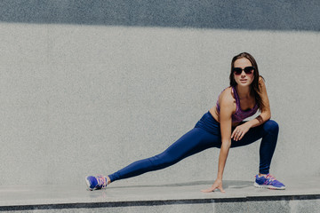 Jogging and fitness concept. Young active female stretches legs muscles before running exrcices, goes in for sport every morning, wants to be fit and healthy, wears shades, purple top and leggings