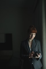 Businesswoman using cell phone while standing indoors