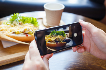 Young woman taking photo of her lunch in cafe or restaurant.
