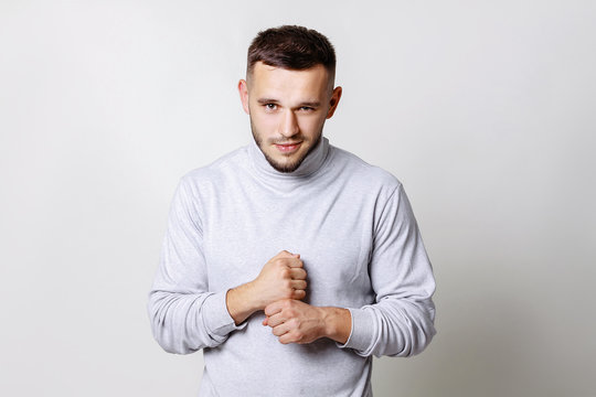Close up portrait of a young man smirking. Handsome in white turtleneck beats his fist on the fist standing on grey background copy space