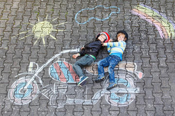 Creative leisure for children: two little funny friends in helmet having fun with motorcycle picture drawing with colorful chalks. Children, lifestyle, fun concept