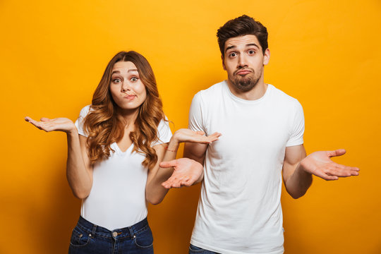 Image of happy young people man and woman in basic clothing throwing up arms with puzzlement, isolated over yellow background