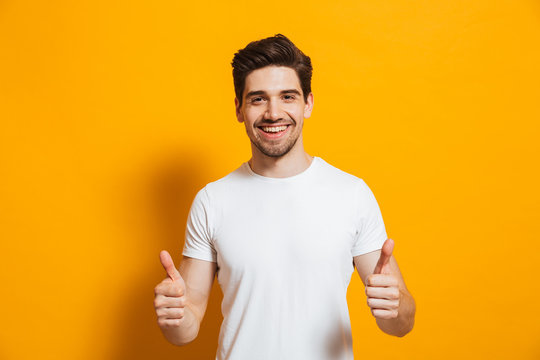 Portrait of cheerful man in basic clothing smiling and showing thumbs up at camera, isolated over yellow background
