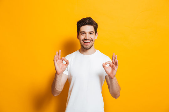 Portrait of handsome excited man in basic clothing smiling and showing ok sign at camera, isolated over yellow background