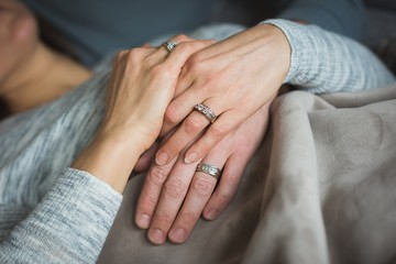 Close up of couple holding hands indoors