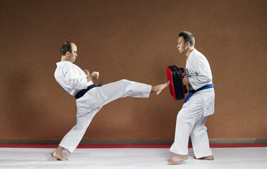 A sportsman with a black belt beats his kick on the simulator