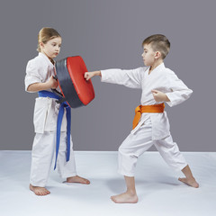 A boy trains a punch on a simulator on a gray background