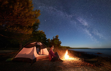Night camping on sea shore. Smiling woman hiker sitting relaxed in front of tourist tent at campfire under amazing sky full of stars and Milky way. Clear blue water and green forest on background