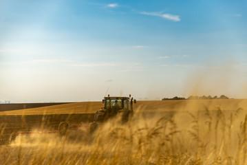 Le fermier sur son tracteur agricole prépare sa terre pour aérer les sols en formant de la fumée de poussière