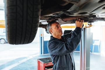 Experienced mechanic working in his garage