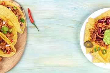 Mexican food with copy space, overhead photo of hot spicy tacos and nachos on teal