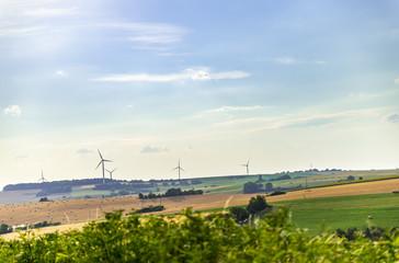 Vue de campagne en Moselle avec ses champs agricoles et des éoliennes sur l'horizon