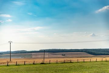 Paysage de campagne avec des champs et une clôture, des fils électriques aériens traversent la vue
