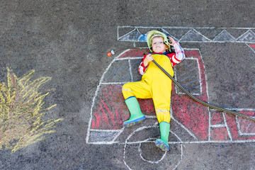 Little kid boy in fireman uniform having fun with fire truck picture drawing with colorful chalk on asphalt