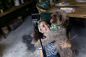 young beautiful woman taking a selfie with her spanish water dog in a cafe. Daytime, love for animals concept and lifestyle