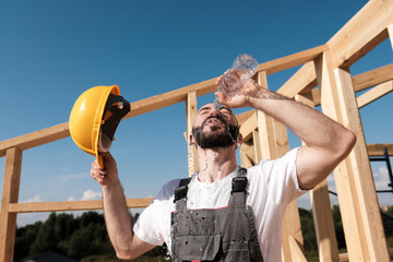 The man builder sits on the edge of the roof of the frame house, in a yellow helmet and gray overalls and a white T-shirt. He pours water on the head from the bottle.