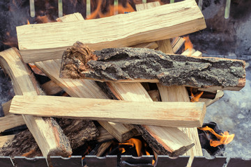 Firewood is burning in the grill in the open air