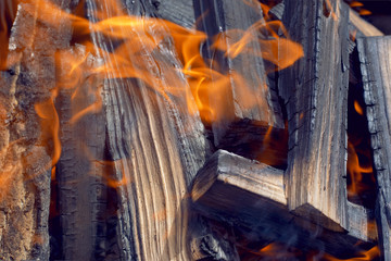 .A beautiful background of black burning firewood in flame and ash.Close-up