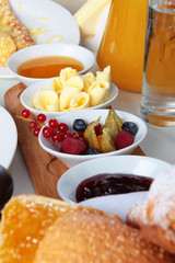 Breakfast at the hotel or at home. Gem, honey, berries, oil and decanters with juice, milk and water on the table. Hotel and restaurant business. Photo in the interior.