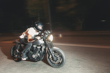 The biker is riding a motorcycle on the highway at night. Speed.