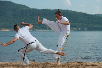 Men train capoeira on the beach - concept about people, lifestyle and sport.