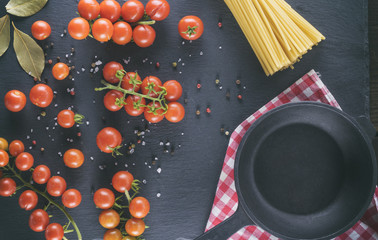 empty cast iron round frying pan and ripe red cherry tomatoes