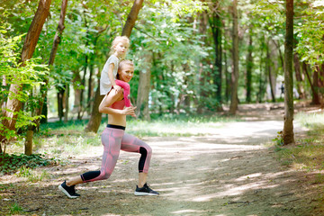 Mother and daughter exercise together in park. Piggyback, Sport, Family, Healthy lifestyle