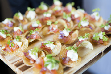 Close-up of appetizers with onions, cheese, tomatoes and sour cream on a potato chip on a board, at an event, Canada