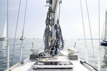 View from the deck of the yacht on the mast and rigging, sea and boats in the background.