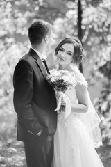 Happy wedding couple. Bride and groom smiling and embracing in the park. Sunny summer day. Black and white image
