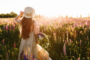 Young woman in straw hat and dress with bouquet of lupine flowers, rear view in sunset field